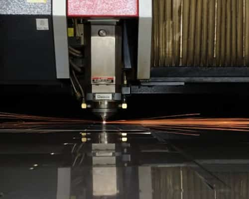 sparks flying as a machine uses laser to cut into a thick piece of metal